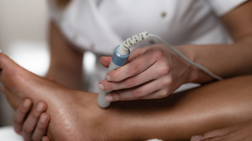 Woman giving laser therapy on ankle