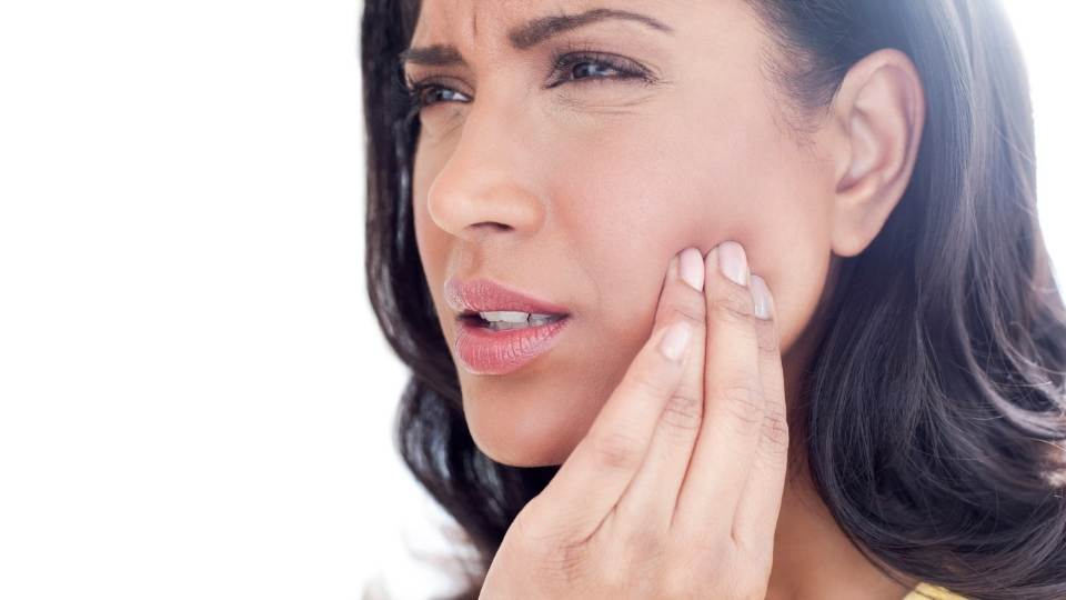 Woman with jaw pain holding jaw