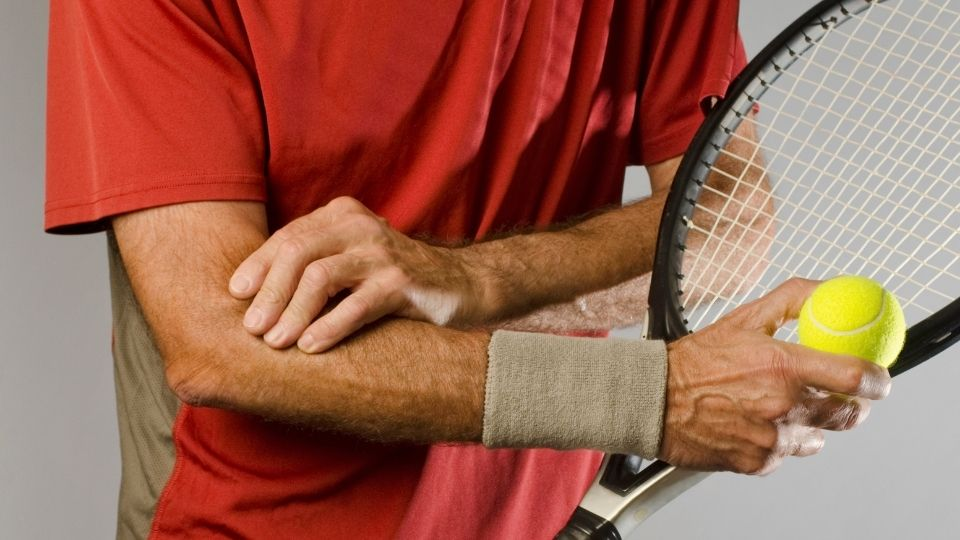 Man with tennis racket and elbow pain