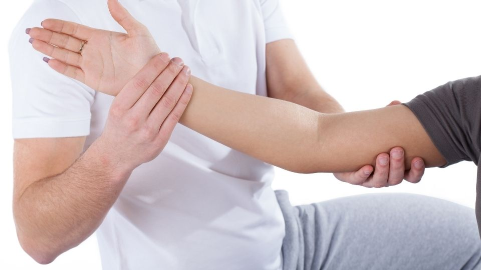 Man receiving physio care for elbow pain